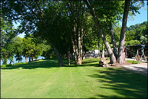 large yard between riverfront campsites and the Ohio River